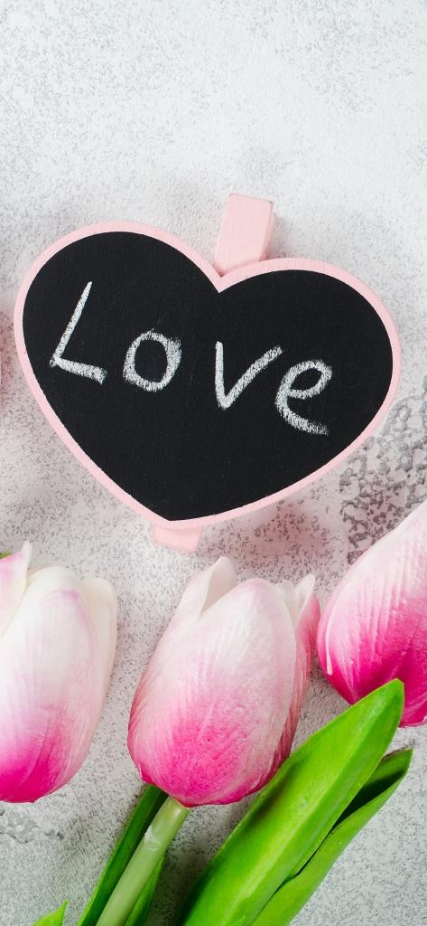 iPhone achtergrond met roze tulpen en bordje met tekst love